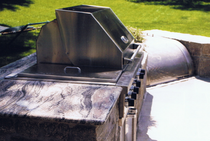 Outdoor cooktop and granite countertops with fire pit and stainless steel cover
