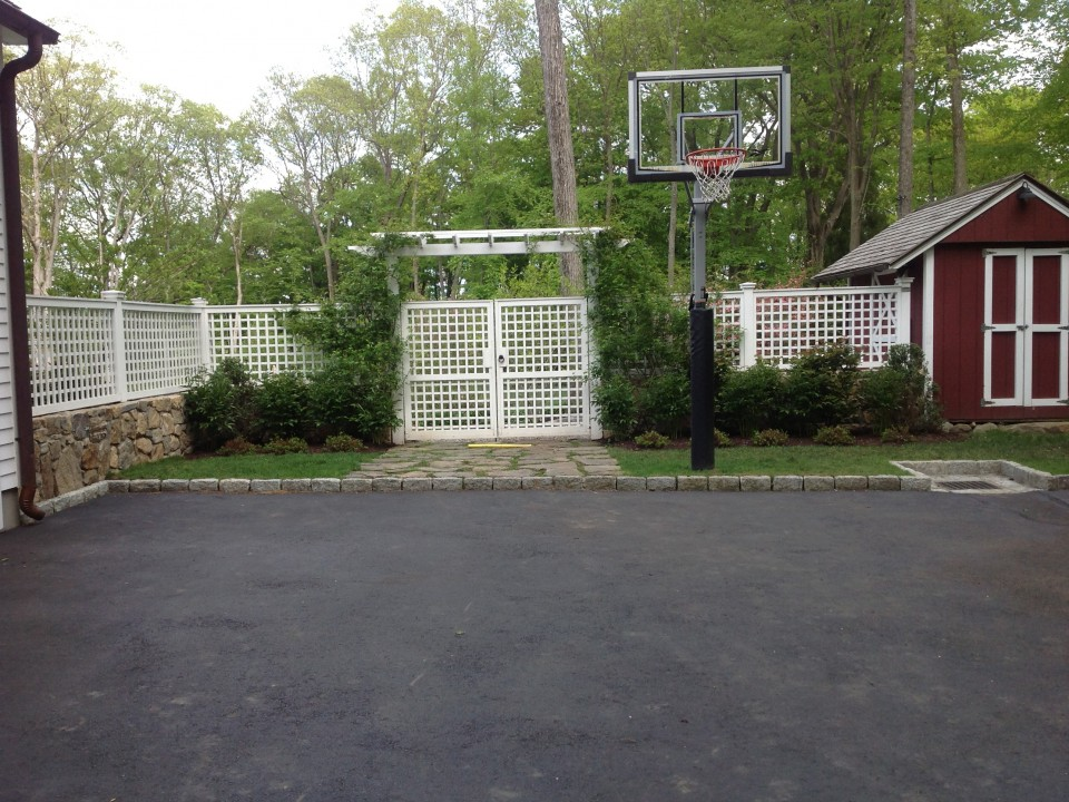 Sports court and fieldstone wall with fence, gate, arbor and plantings